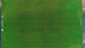 Aerial view of large lawn mower cutting green grass in a soccer field. 4K. stock footage