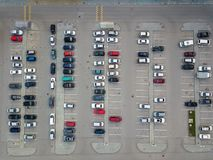Aerial view of a large number of cars of different brands and colors standing in a parking. Lot near the shopping center in a chaotic manner. Parking divided by Stock Images