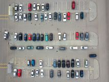 Aerial view of a large number of cars of different brands and colors standing in a parking. Lot near the shopping center in a chaotic manner. Parking divided by Royalty Free Stock Photos