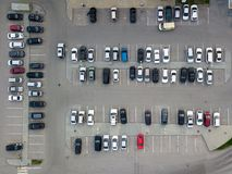 Aerial view of a large number of cars of different brands and colors standing in a parking. Lot near the shopping center in a chaotic manner. Parking divided by Royalty Free Stock Images