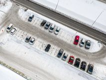 Aerial view of a large number of cars of different brands and colors standing in a parking covered with snow lot near the shopping stock image