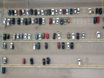 Aerial view of a large number of cars of different brands and colors standing in a parking. Lot near the shopping center in a chaotic manner. Parking divided by Royalty Free Stock Photography