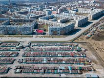 Aerial view of a large number of iron garages for cars with colored roofs standing in close to each other near the road fenced. Parking of vehicles for the stock photos