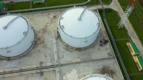 Aerial view of large oil refinery facilities with tanker, tank. Useful for industrial media usage.Taken from sky in. Flyby using a drone in the late afternoon stock video footage