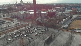 Aerial view of large parking with cars near the modern and historical buildings and tall red chimney in the center of royalty free stock image