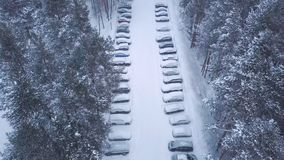 Aerial view of large parking and cars near the trees covered by snow in winter park in evening. Clip. View from above stock photos