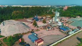 Aerial view of large sand piles and launching of building. 4K. Drone view of concrete factory territory and nearby facilities. Copy space stock footage