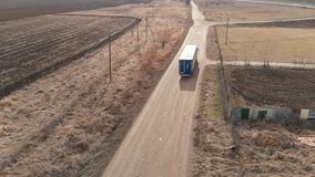 Aerial view of a large truck with a trailer driving along a dirt road in search of a place for a U-turn in the vicinity