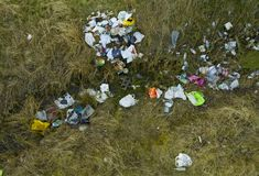Aerial view on leftover garbage polluting green meadow, cans, bottles and shopping plastic bags.  royalty free stock photo