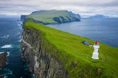 Aerial view of lighthouse at Mykines island in Faroe Islands, North Atlantic Ocean. Photo made by drone from above. Nordic natural