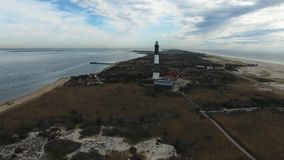 Aerial View of a Lighthouse and Shoreline Close Up on a Sunny Winter Day as Seen by a Drone stock footage