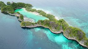 Aerial View of Limestone Island and Marine Lake in Raja Ampat. A beautiful limestone island surrounds a marine lake in Raja Ampat, Indonesia. This remote stock video footage