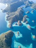 Aerial View of Limestone Islands in Raja Ampat. The amazing limestone islands found in Wayag, Raja Ampat, Indonesia, are surrounded by healthy coral reefs. This stock photography