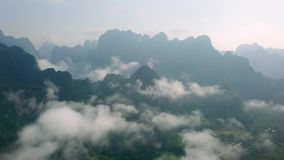 Aerial View of Limestone Rocks in Mist Covered with Lush Tropical Greenery. Top View of Mountains in Krabi and. Suratthani Provinces, Thailand shot with a DJI stock video footage