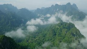 Aerial View of Limestone Rocks in Mist Covered with Lush Tropical Greenery. Top View of Mountains in Krabi and. Suratthani Provinces, Thailand shot with a DJI stock footage