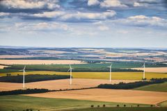 Aerial view of a linear wind farm on colorful fields generating eco energy. stock images