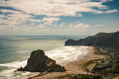 Aerial view on the lion rock on Piha beach. Auckland, New Zealand - March 2, 2017: Aerial view on the Lion rock at sandy Piha Beach under blue sky with white royalty free stock photos