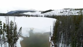 Aerial view of Little Redfish lake in winter while covered with ice. Sawtooth mountains above a frozen Redfish lake in winter stock video footage