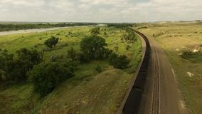 Coal Train Passing Midwest Plains Transportation Infrastructure. Aerial view of a locomotive passing along cars filled with coal moving to market stock footage