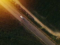 Aerial view of lonely car on the road. Driving towards sunset, drone point of view royalty free stock photo