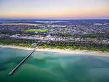Aerial view of long wooden pier stretching into shallow ocean wa. Ter and coastal suburban houses in Melbourne, Australia Stock Photo