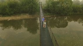 Aerial view Loving Couple on a Wooden Bridge in the Mountains. Aerial view. Loving Couple on a Wooden Bridge in the Mountains. Morning fog stock footage