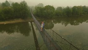 Aerial view Loving Couple on a Wooden Bridge in the Mountains. Slow motion stock video