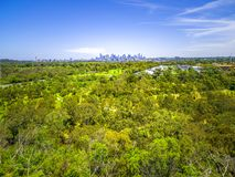 Aerial view of lush green park and Melbourne CBD skyscrapers on bright sunny day. Aerial view of lush green park and Melbourne CBD skyscrapers on bright sunny Royalty Free Stock Image