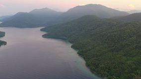 Aerial of Tropical Islands at Dawn in Papua New Guinea. An aerial view of lush island scenery in New Ireland, Papua New Guinea. This remote area is part of the stock video