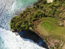 Aerial view of luxury golf course next the cliff, ocean and beach in Bali island, Indonesia. stock photo