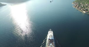 Aerial view of luxury medium cruise ship sailing from port on sunrise. Through the bay stock video