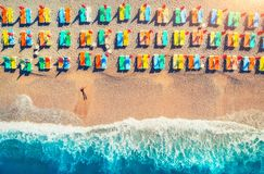 Aerial view of lying woman on the beach with colorful chaise-lounges Royalty Free Stock Photo