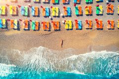 Aerial view of lying woman on the beach with colorful chaise-lounges Stock Photos