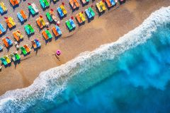 Aerial view of lying woman with swim ring in the sea in Oludeniz, Turkey. Summer scene. With young girl, blue water, waves and sandy beach with colorful chaise Royalty Free Stock Photos