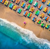 Aerial view of lying woman with swim ring in the sea. In Oludeniz, Turkey. Summer scene with young girl, blue water, waves and sandy beach with colorful chaise stock photo