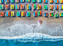 Aerial view of lying woman with swim ring in the sea. In Oludeniz, Turkey. Summer seascape with girl, azure water, waves and sandy beach with colorful chaise Stock Image