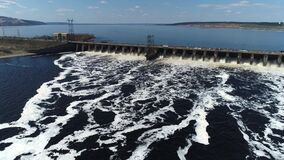 Aerial view, made by drone, of a hydroelectric power plant dam. The force of the water in the spillway is observed.