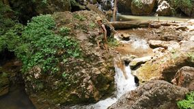 Aerial view of a male traveler in a straw hat and a backpack climbs on a rock against the backdrop of a majestic. Waterfall in the woods among the rocks. Travel stock video