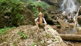 Aerial view of a male traveler in a straw hat and backpack sits on a rock against the backdrop of a majestic waterfall. In the woods among the rocks. Travel stock footage