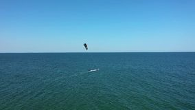 Aerial view man kite surfing in turquoise sea. Drone view flying ove kite surfer. Kite surfer surfing crystal clear water. Black S stock video