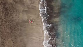 Aerial view of a man in red shorts lies on the beach with black sand. Tenerife, Canary Islands, Spain. Aerial view of a man in red shorts lies on the beach with stock footage