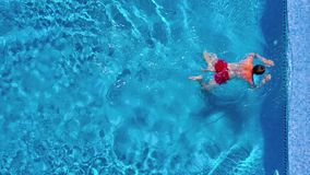 Aerial view of man in red shorts swims in the pool and get out of it stock footage