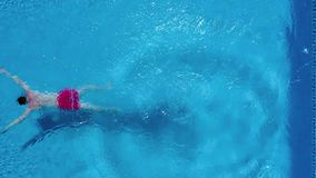 Aerial view of man in red shorts swims in the pool stock video footage
