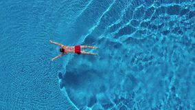 Aerial view of man in red shorts swims in the pool stock footage