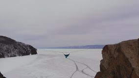 Man sitting in a hammock mounted at high altitude over a frozen lake. stock video footage