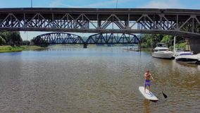 Aerial View of Man on Stand Up Paddle board on River. An aerial wide view of a man on a stand up paddle board on a Pennsylvania river in the summer. Pittsburgh stock video