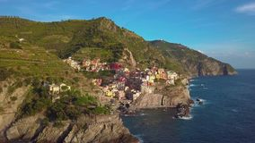 Aerial view of Manarola village on cliff rocks and turquoise sea. Stunning view of beautiful and cozy town in Cinque stock footage