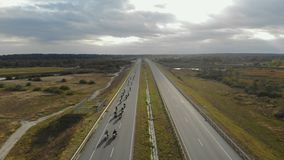 Aerial view of many motorcyclists driving on the highway. Column bikers on motorcycles moving on a road trip stock video