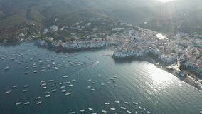 Drone flight over bay of town Cadaques at sunset. Aerial view of many yachts in beautiful bay of coastal resort town Cadaques on Cap de Creus peninsula. Drone stock footage