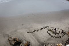 Aerial view of marriage proposal being written in the sand on the beach below the cliff Royalty Free Stock Photo